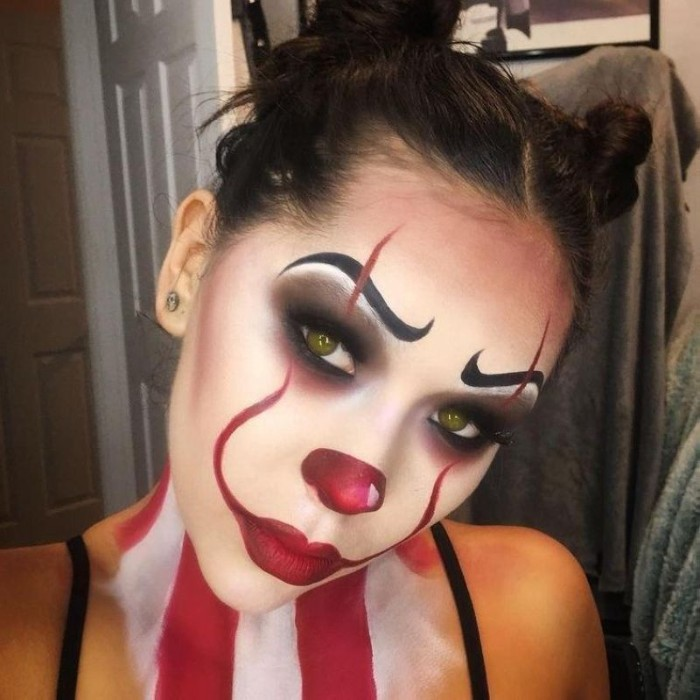 pennywise clown face paint, inspired by the film it, worn by a young woman, with dark hair and green eyes