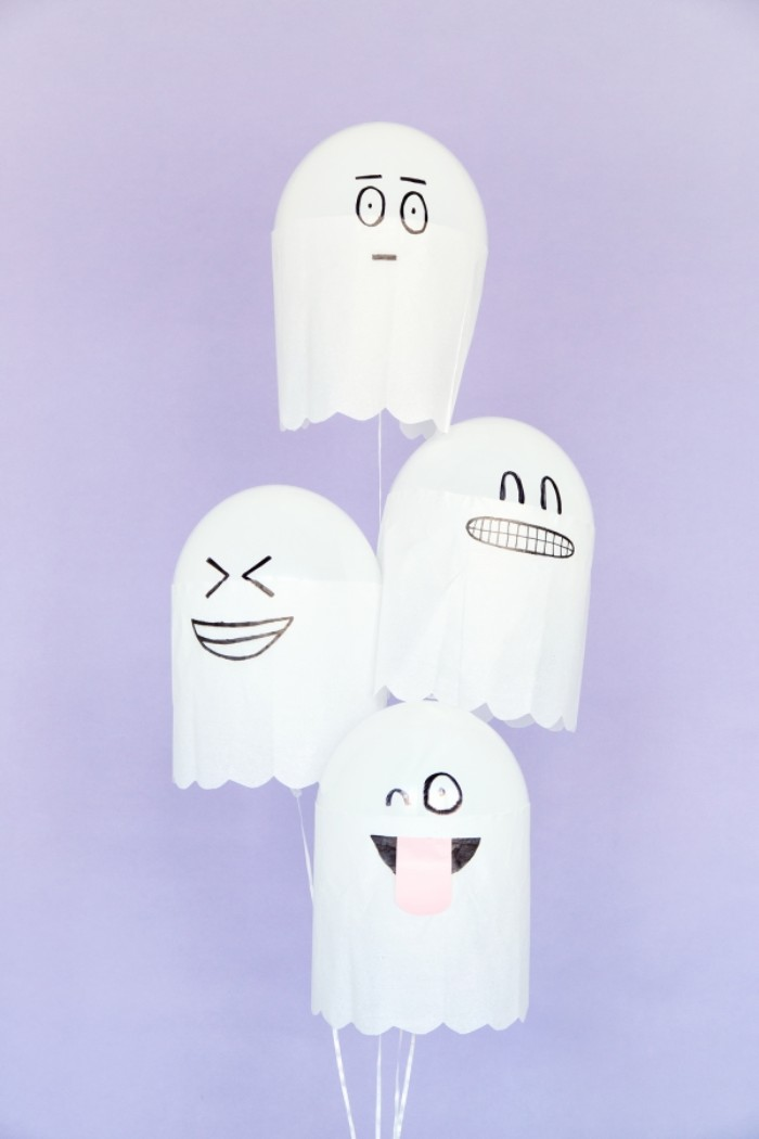 bunch of white balloons, decorated with white paper, to look like ghosts, with silly hand-drawn faces