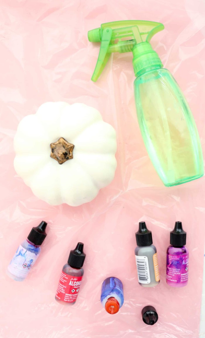 clear green plastic spray bottle, near a small white fake pumpkin, and five bottles of paint, in different colors, halloween pumpkin decorations