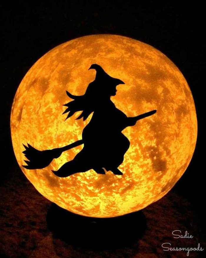 halloween witch decorations, black outline of a witch, flying on a broomstick, stuck to a glowing, moon-like beige lamp