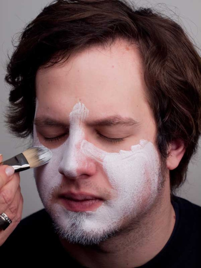 clown face paint, recreating the look of the joker from batman, hand applying white paint, on the face of a young man, with wavy brunette hair