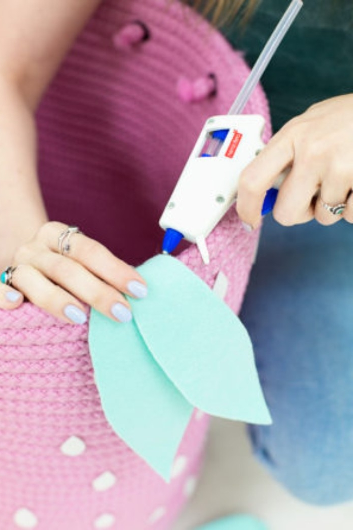 glue gun being used to stick two mint green, felt leaf-shapes, to the rim of a large, pink clothes basket, decorated with white, seed-like shapes to resemble a strawberry, how to decorate a bedroom