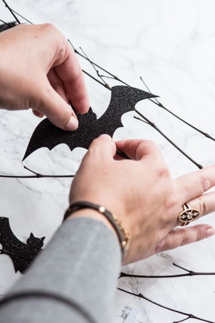 gluing a black, bat-shaped card cutout, onto a dark brown, thin dried branch, placed on a light marble surface