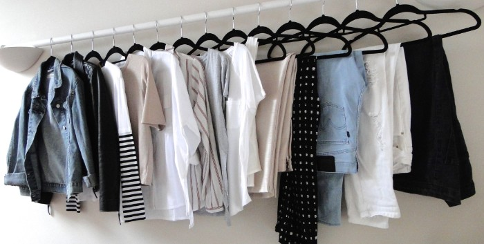 trousers in different colors, jeans and t-shirts, jumpers and shirts, a blue denim jacket, capsule wardrobe planner, with black hangers