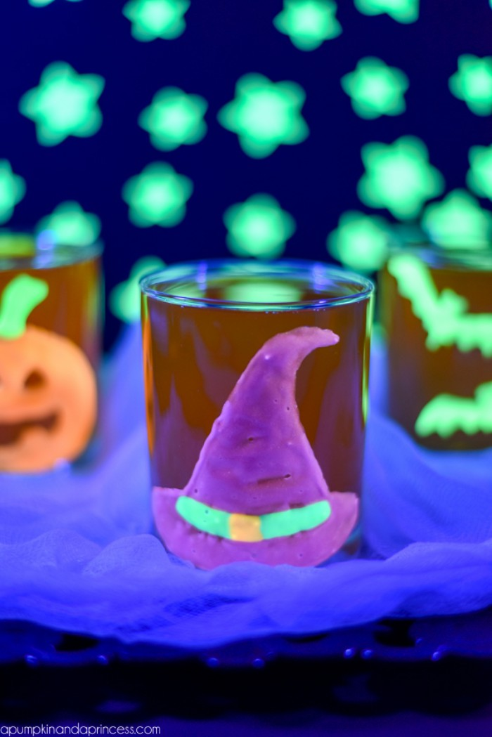 purple witch's hat, glow-in-the-dark sticker, with neon green, and orange details, stuck on a glass, halloween party decoration ideas, more glowing shapes in the background, bats and stars