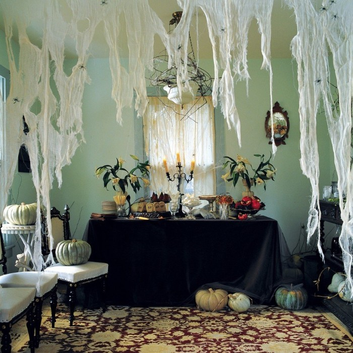haunted house decorations, huge fake cobwebs, hanging over a table, with a black tablecloth, two vases with wilted flowers, and an antique candlestick