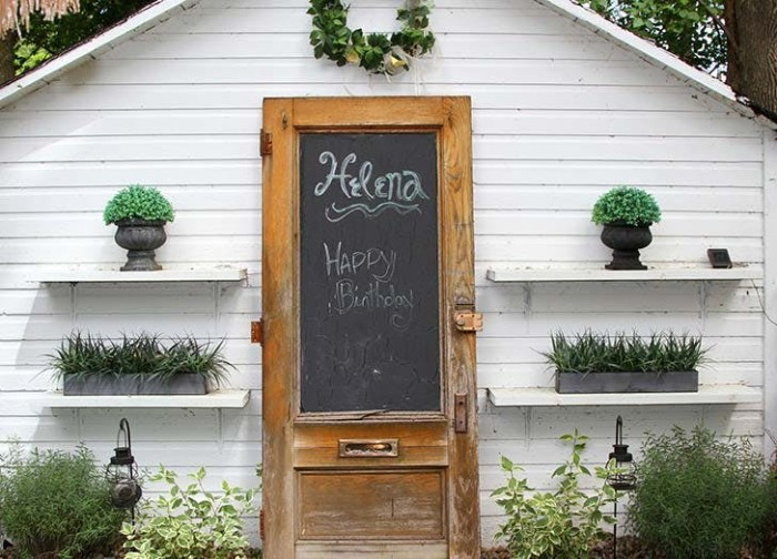 blackboard attached to the vintage wooden door, of a white shed, decorated with several potted plants, garden shed ideas