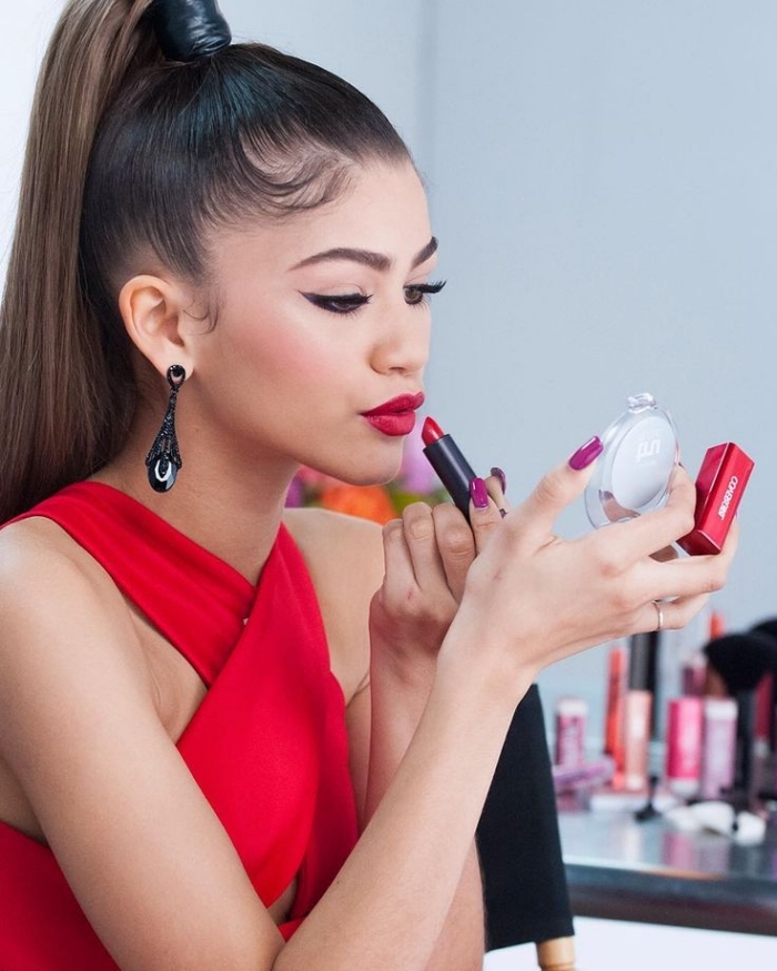 high ponytail worn by a brunette woman, dressed in a red gown, with black eyeliner, and violet nail polish, applying red lipstick