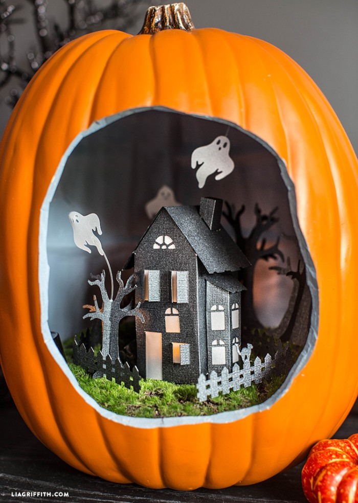 decorative ornament shaped like a pumpkin, with a large hole, revealing a small paper house inside, decorated with three paper ghosts, halloween decorations