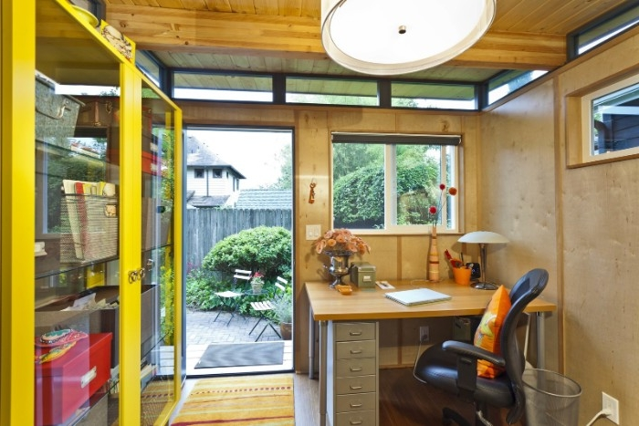 desk and an office chair, inside a small garden shed, containing a yellow cupboard, she shed interiors
