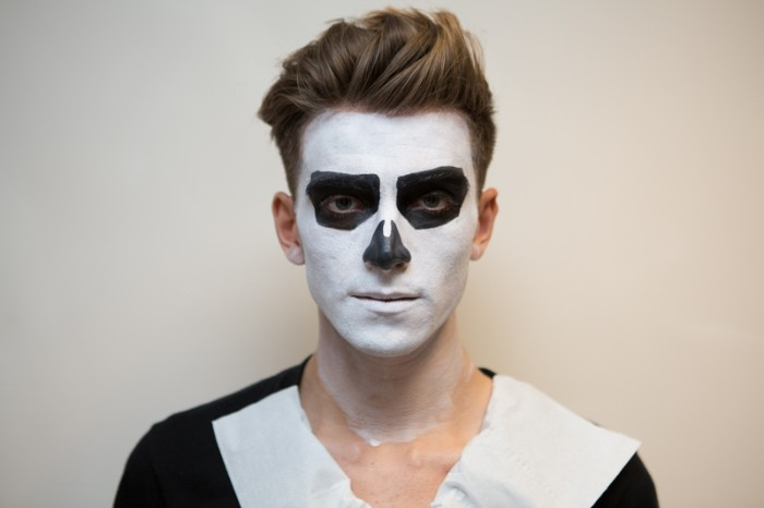 drawing skeleton features, with black and white paint, on the face of a young man, with brunette hair
