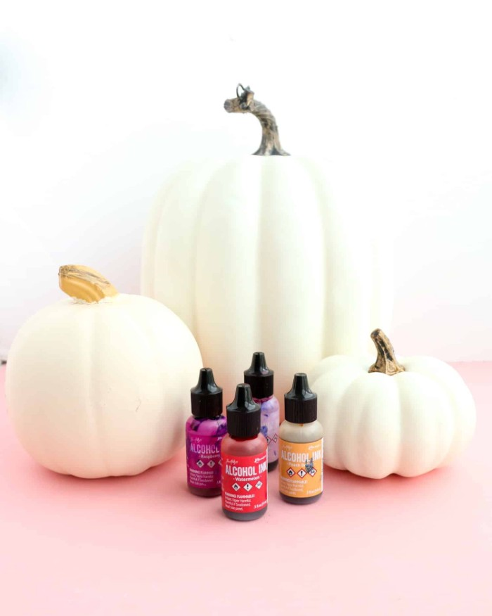 halloween pumpkin decorations, three white fake pumpkins, placed on a pale pink surface, near four small bottles of paint, in differen colors