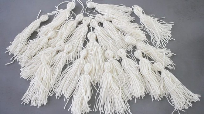 bedroom makeover, many DIY tassels, made from white yarn, and placed on a dark grey surface, handmade tassel chandelier tutorial