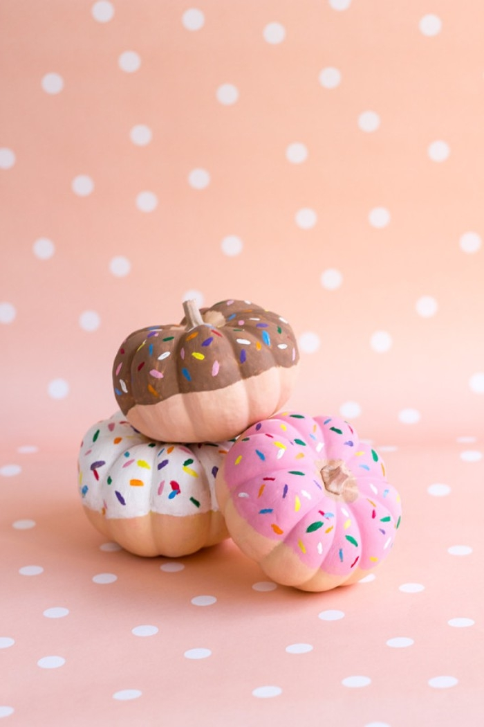 small orange pumpkins, hand-painted to look like three different donuts, on a peach-colored background, with white polka dots, how to decorate your room