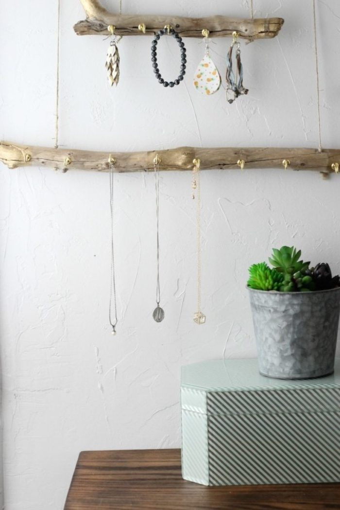 finished hanging jewelry stands, made from driftwood, with spray-painted metallic gold details, and gold cup hooks, holding bracelets and pendants, room makeover