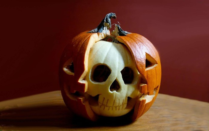 carved pumpkin with two layers, orange jack-o-lantern, cut to reveal a smaller, white pumpkin within, carved to look like a skull, skeleton pumpkin