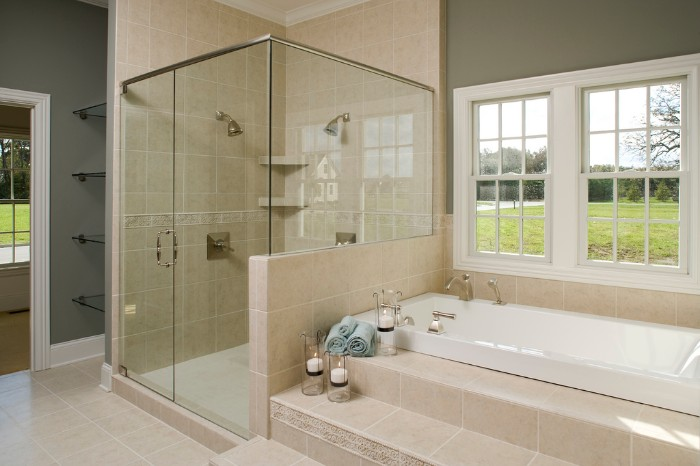 cream tiles decorating a room, with khaki green walls, and white paneling, master bathroom remodel, glass shower cabin, and an elevated tub