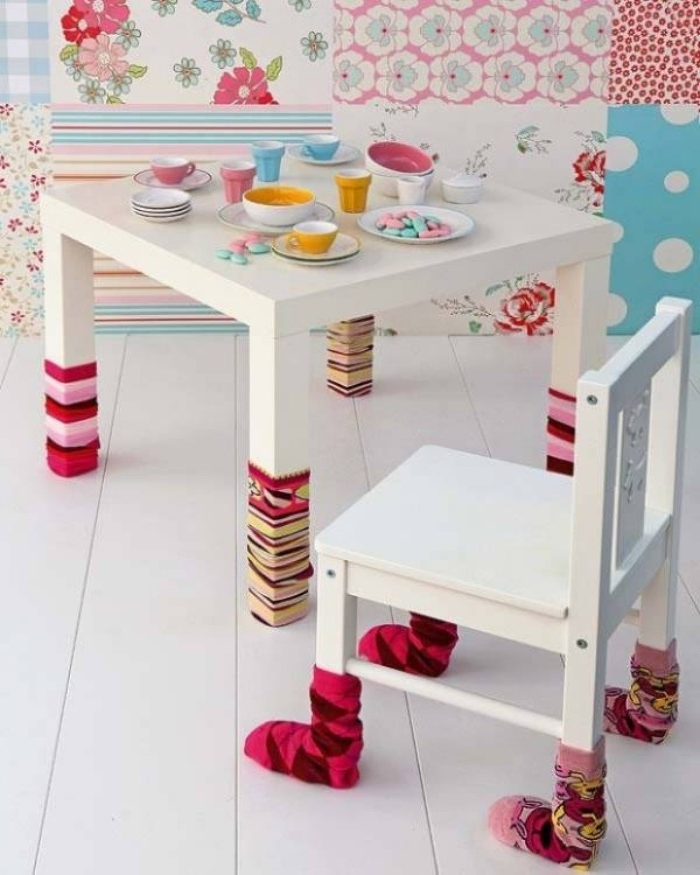 childrens' room DIY decor, multicolored wallpaper with different patterns, small white table with matching chair, all legs covered in colorful used socks