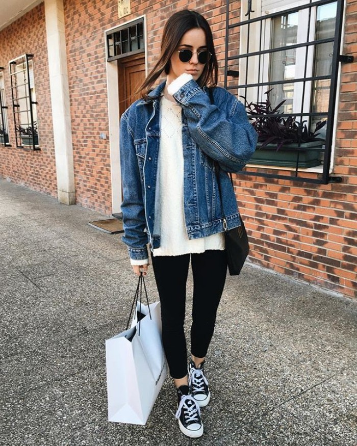 wearing capsule closet items, black leggings and a white blouse, oversized denim jacket, and classic converse sneakers, on a young brunette woman, wearing sunglasses