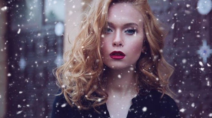 snow falling aroud a young woman, with curly blonde hair, wearing dark red lipstick, and a black top