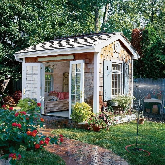 tiled roof on a wooden shed, with open double doors, and windows with wooden shutters, shed ideas, garden with sprinkler, and many plants