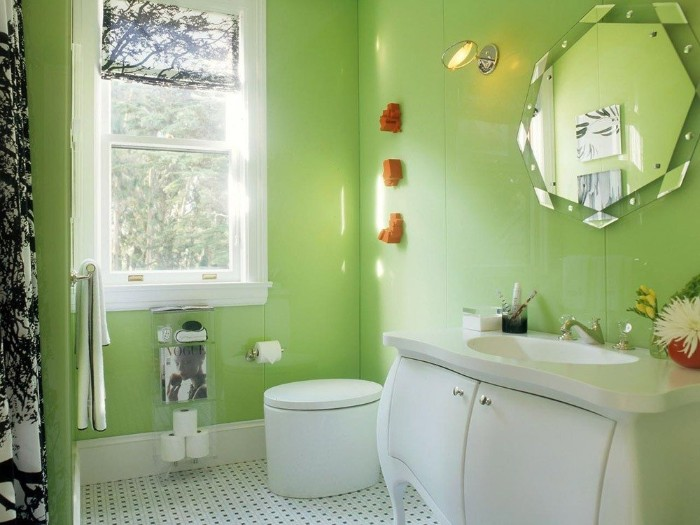 matcha green paneled walls, in a bright bathroom, with a window, a modern oval toilet, and a white cupboard, with an inbuilt sink