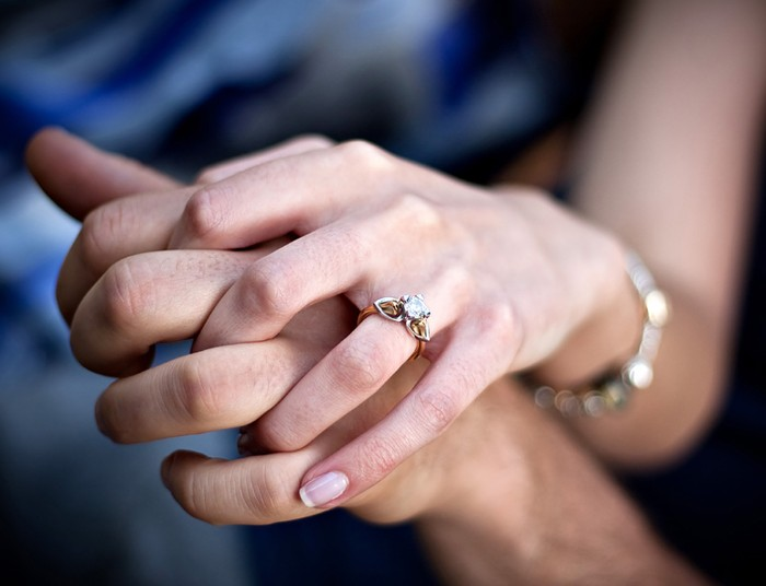 diamond engagement rings, close up of two linked hands, the one on top is wearing a ring, with a white diamond