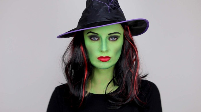 highlights in red, in the black hair, of a woman, wearing green witch face paint, and wearing red lipstick, and a witch's hat