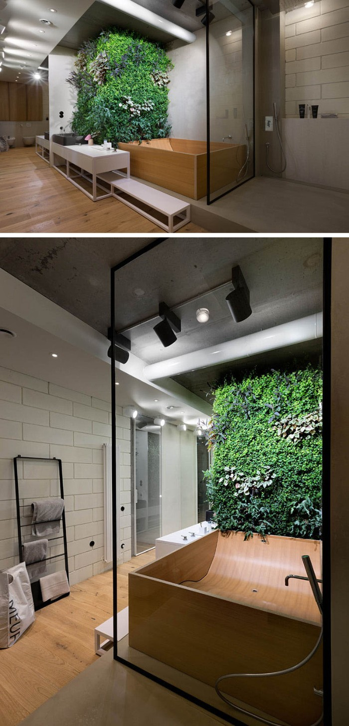 wall covered in green plants, near a bathtub, made from pale beige wood, inside a room with white tiled walls, and a laminate floor, master bath remodel