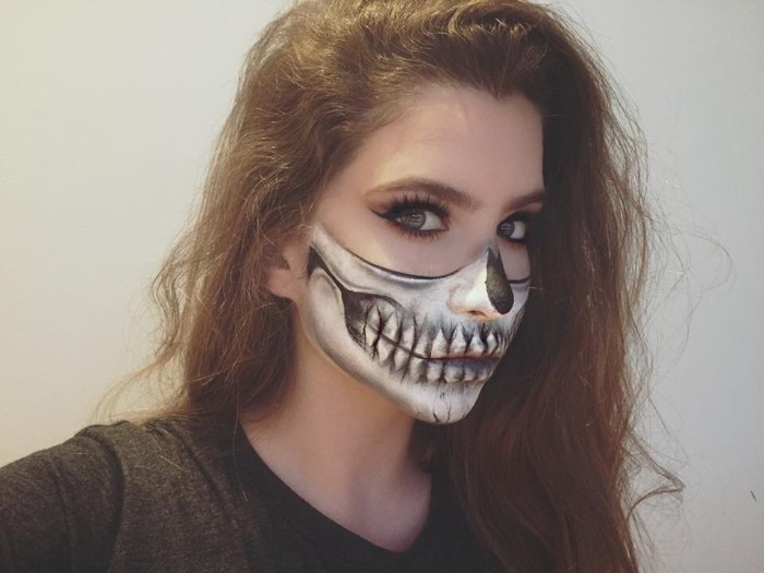 half skeleton face paint, worn by a young woman, with long brunette hair, wearing fake lashes, and black eyeliner