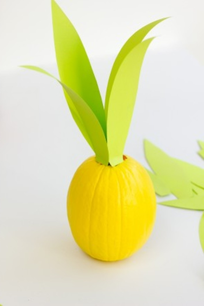 sticking four long, light green leaf-shaped cutouts, on top of an oval pumpkin, spray-painted in yellow, diy bedroom décor, make your own pineapple
