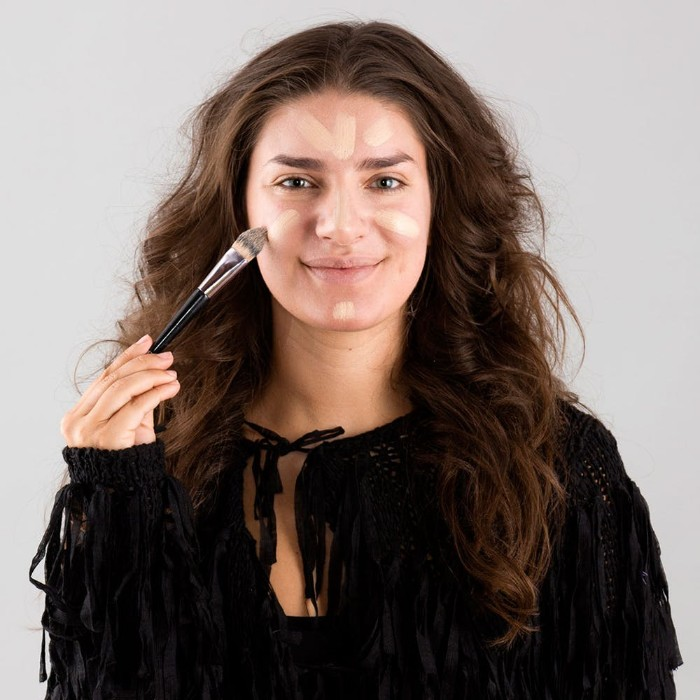 smiling brunette woman, with long and wavy brunette hair, applying foundation on her face, using a brush, halloween face paint how to