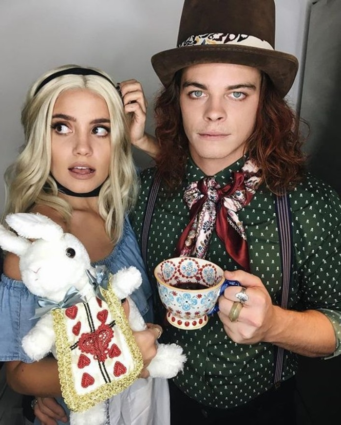 blue-eyed man, dressed like the mad hatter, posing with a woman, dressed like alice, holding a stuffed white rabbit, cute couple halloween costumes