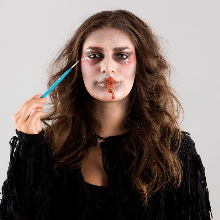 teal brush used to add special effects makeup wax, near the corners of the eyes of a young woman, with zombie face paint, and brunette wavy hair