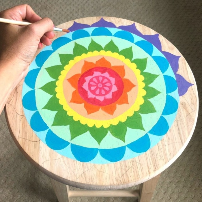 almost finished flower mandala painting, in rainbow colors, diy room decor, with many details, hand adding blue paint with a brush