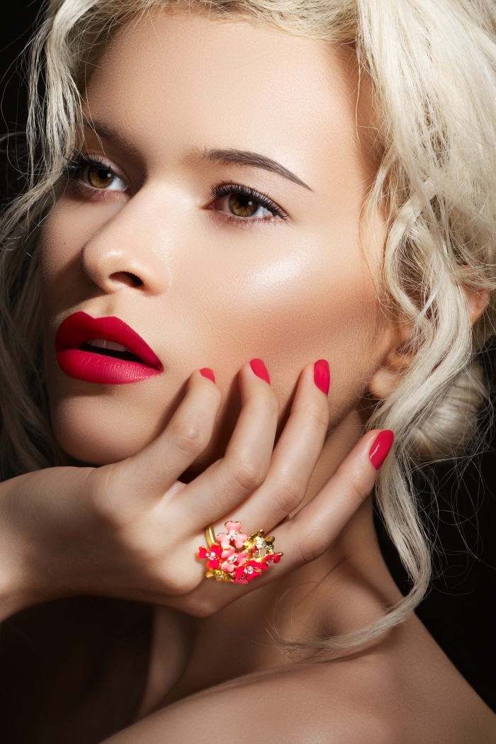 platinum blonde woman, with brown eyes, wearing coral red lipstick, and matching nail polish, holiday makeup, pale pink blush, and an ornamental floral ring