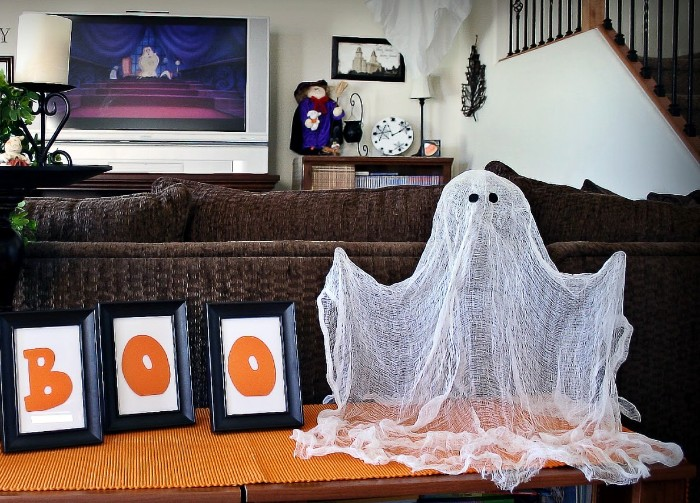 the letters B O O, written in orange, in three black frames, on a table near a ghost decoration, made from gauze and glue, scary halloween decorations