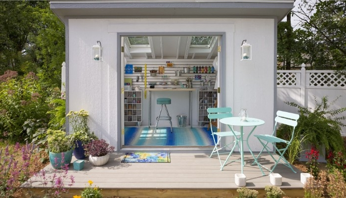 she shed interiors, small white structure with open doors revealing a striped blue and white rug, a blue stool, and various shelves with tools