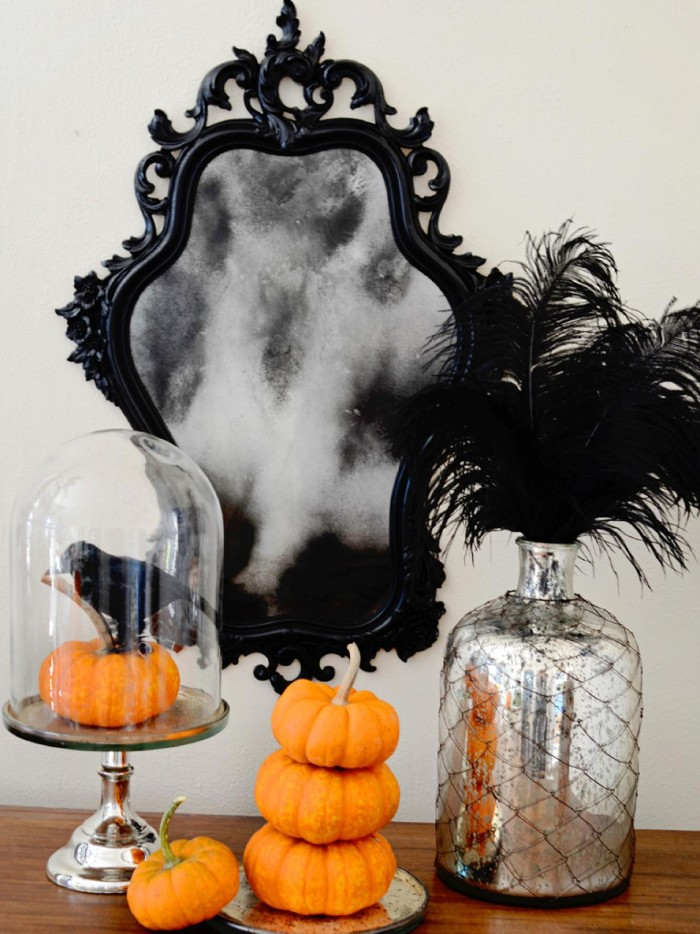 baroque frame in black, on a mirror, decorated with an image of grey smoke, haunted house decorations, several small pumpkins, a silver bottle with black feathers, a glass dish with a pumpkin, and a crow statuette