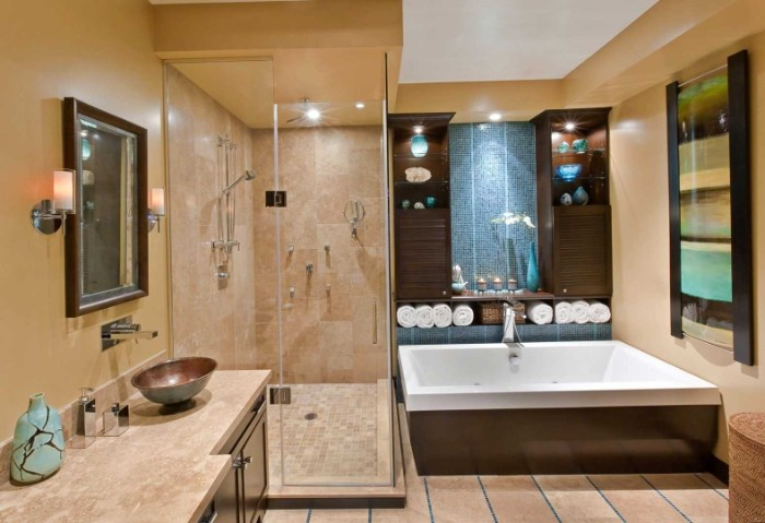 blue and beige, and dark brown bathroom, containing a large square tub, and a glass shower cabin