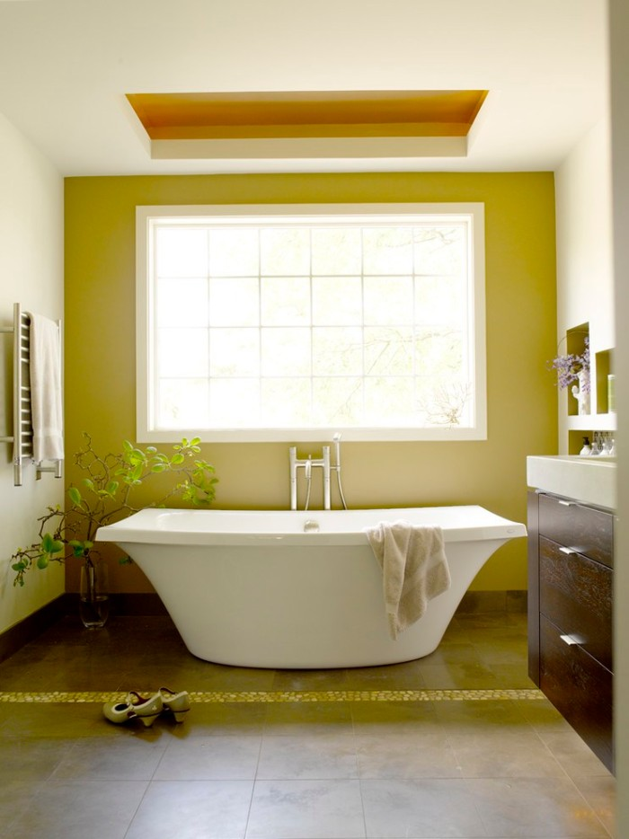 rectangular window with a white frame, on a mustard yellow, bathroom accent wall, in a white room, containing a bathtub