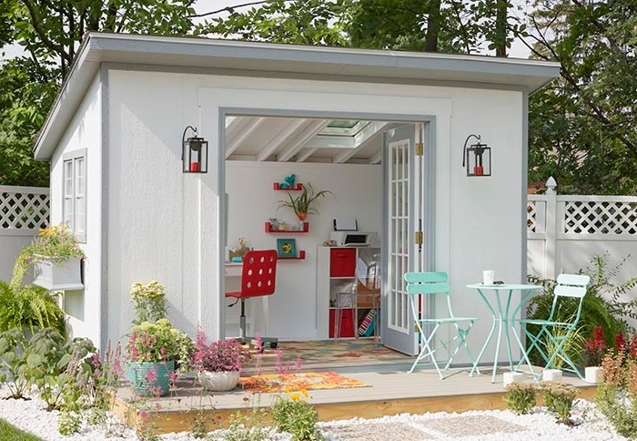 table and two chairs, in front of a white shed, with open doors, revealing a red modern chair, a multicolored rug, and some shelves inside, she shed interiors in red and white