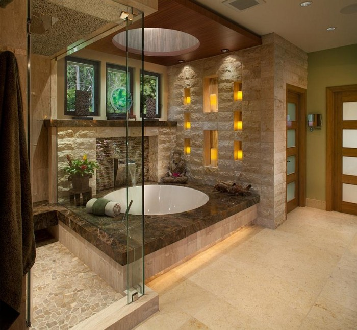 eight candles decorating the wall, of a spa-like bathroom, with pale creamy tiled floor, round white elevated bathtub