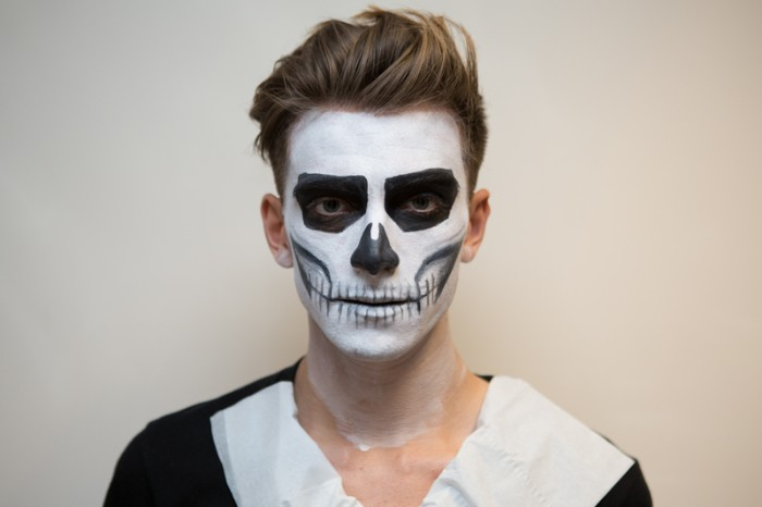 jaw bones and teeth, and other skeleton features, drawn on the face of a young man, with black and white paint