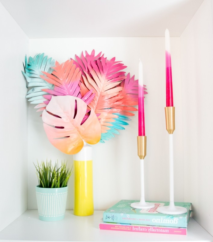 diy room decor, several plastic palm leaves, spray painted in neon pink, yellow and blue, and placed in a yellow and white vase