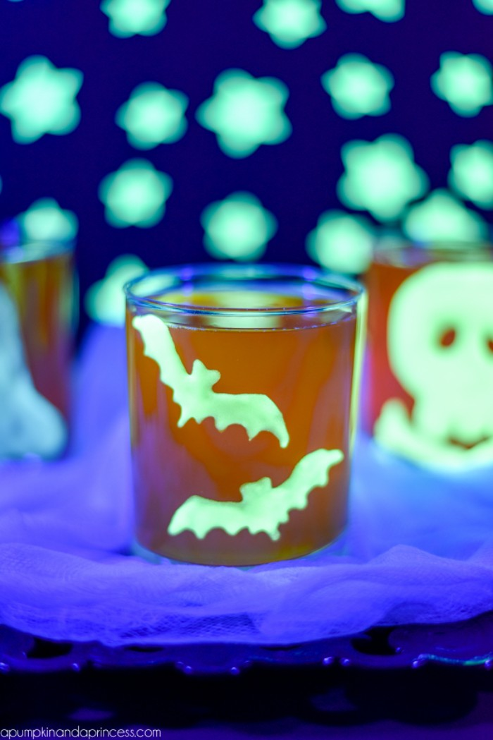 a pair of bats, painted in a glow-in-the-dark neon green color, and stuck on a small orange glass, halloween party decoration ideas, glowing stars in the background
