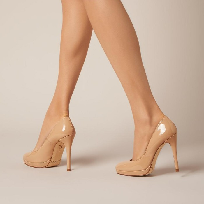 high-heeled pumps, in nude beige color, worn by a pair of pale, slim female legs, what is a capsule wardrobe, essential shoes for women