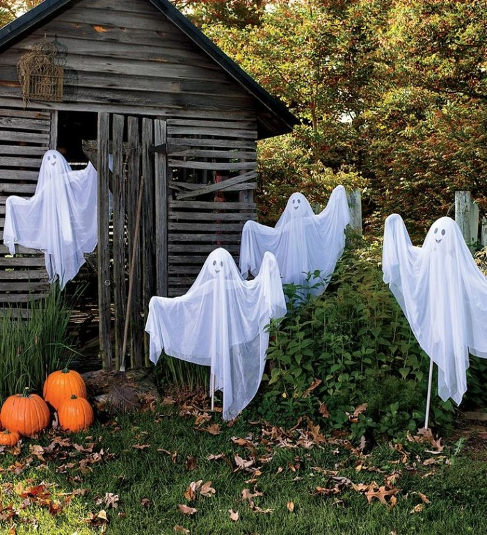 ghosts made of sheer fabric, stuck on wooden poles, with arm-like parts, and simple hand-drawnfaces, in a garden with a broken, old wooden shed, scary outdoor halloween decorations