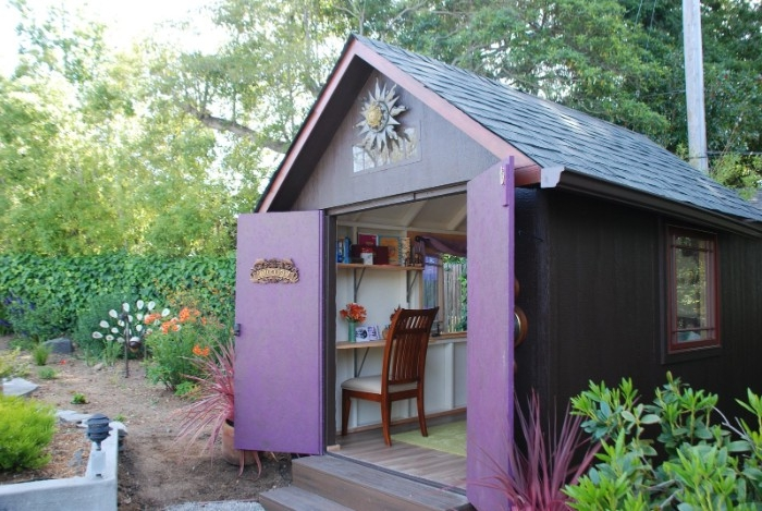 purple hut with blue roof, garden shed ideas, open double doors reveal a wooden chair, and several shelves inside