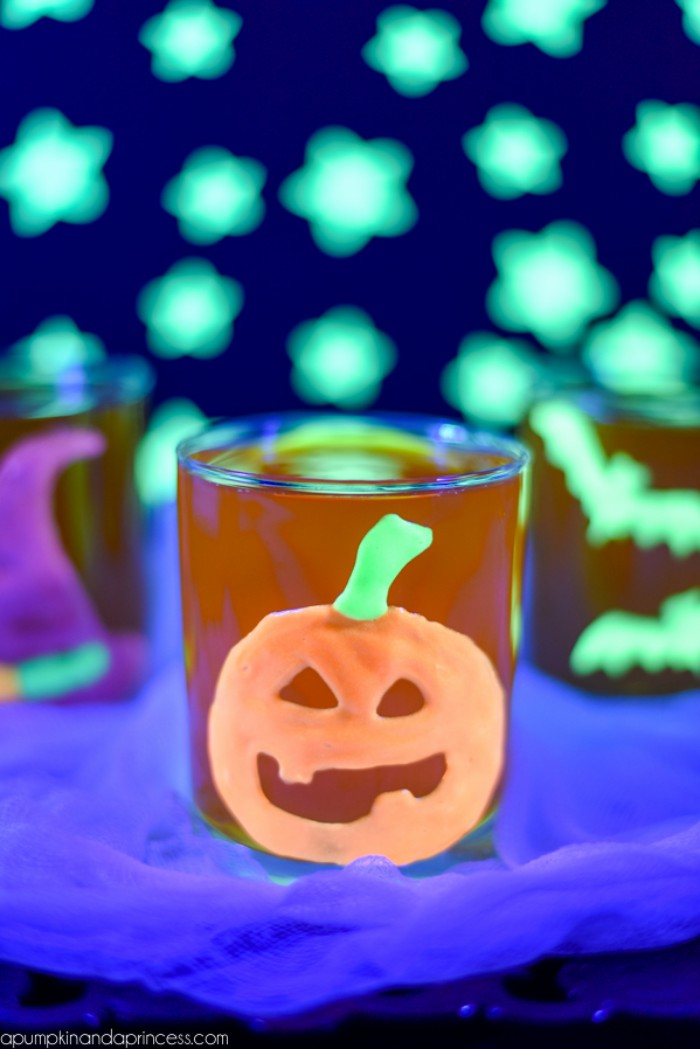 glow-in-the-dark pumpkin sticker, in orange and green, decorating a small orange glass, halloween decorations, more glowing shapes in the background